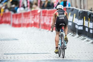 Back of Rebecca Robisch from Germany cycling in rain at...