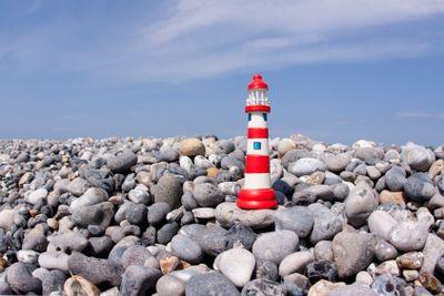 Small model lighthouse on flintstone along the coast