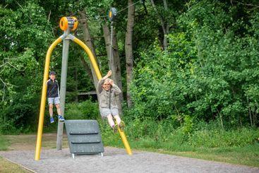 Mamma med barn åker linbana på lekplats i Järfälla.