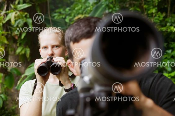 Pretty Woman with Binoculars and Man with Telescope in...