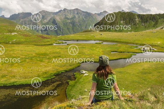 Young woman hiker enjoy the view on mountain peak cliff...