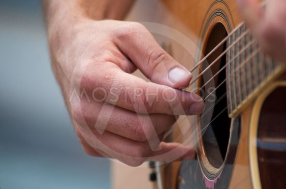 hand of musician on folk guitar in the street