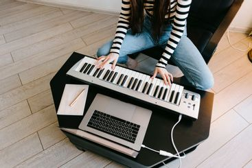 Young caucasian woman learns to play the piano keys...