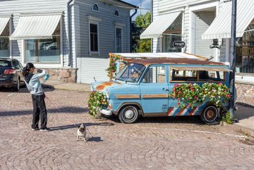 HAMINA, FINLAND - Asian woman with her dog taking a photo