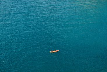 Two people row oars in one yellow-red kayak against the...