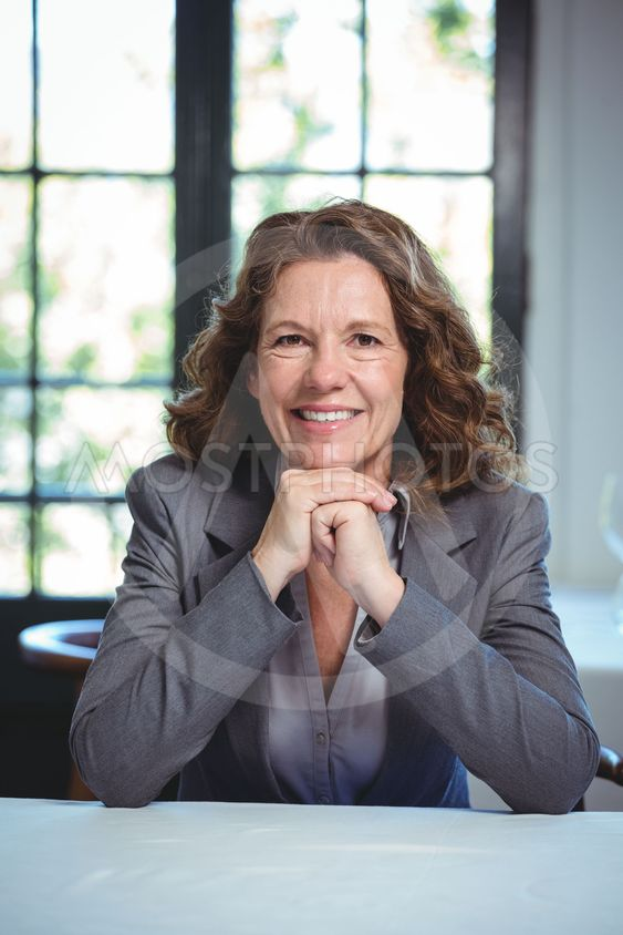 Smiling businesswoman leaning on a table