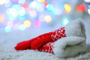 Red woolen mittens on a white background and bokeh