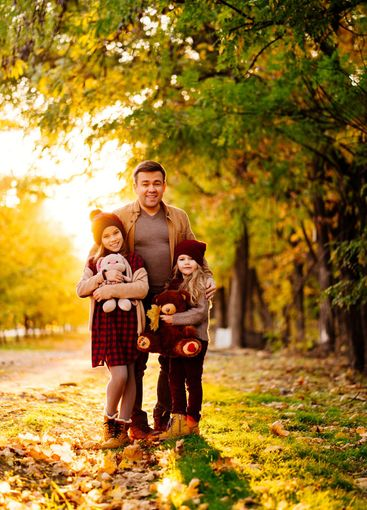 setting sun. dad with daughters walking in autumn Park....
