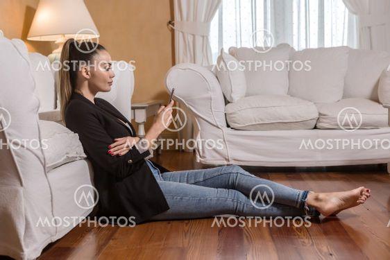 Barefoot businesswoman using smartphone on floor