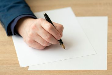 Closeup of hand of a businessman, writing a letter