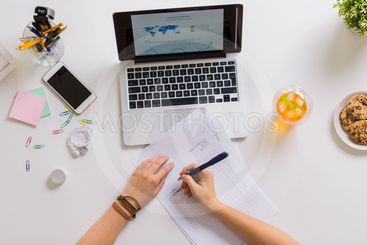 hands with papers and laptop at office table