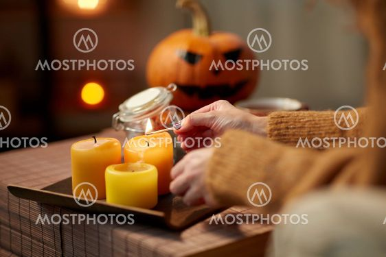 hand with match lighting candle on halloween