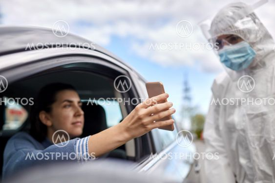 woman in car showing phone to healthcare worker