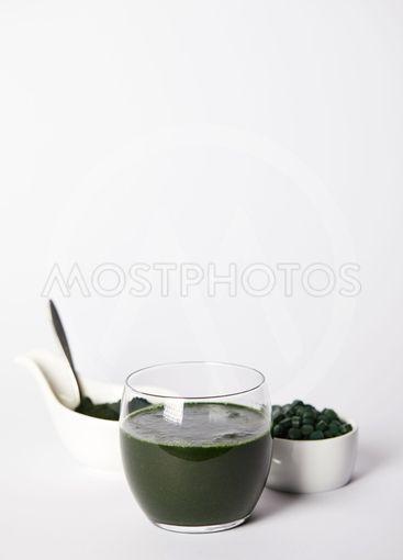 fresh spirulina drink in glass, spoon, spirulina powder...