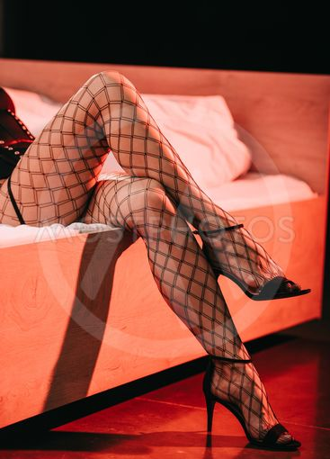 cropped view of sexy prostitute in mesh stockings and...