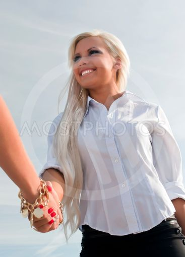 Beautiful blonde girl shakes hands with another girl