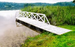 white wooden jetty at the lake in summer