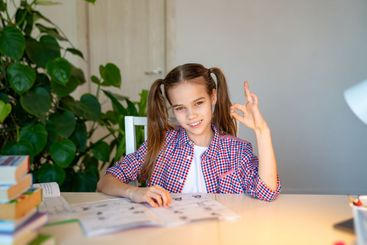teen schoolgirl in a plaid shirt doing homework