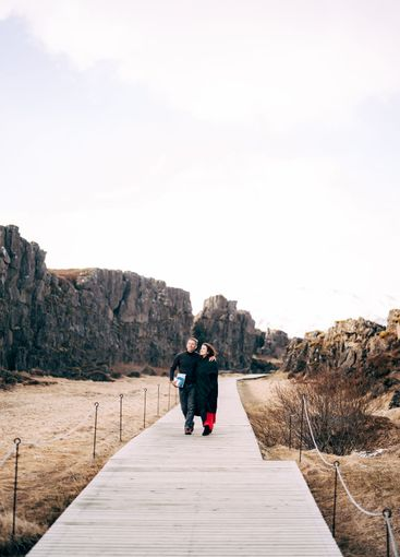 A guy and a girl are walking down the road in the Silfra...