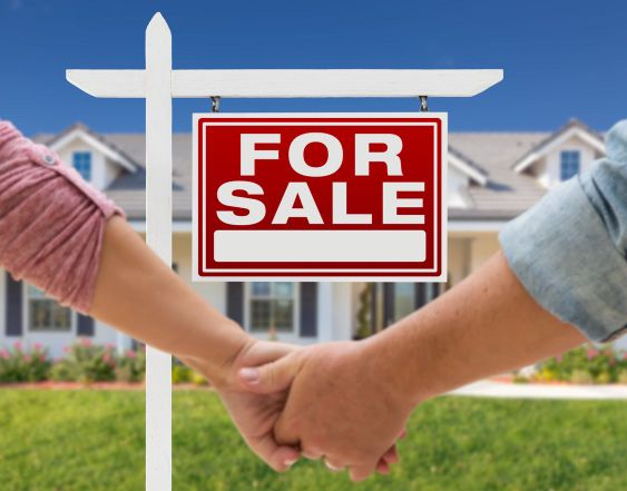 Couple Holding Hands In Front of New House