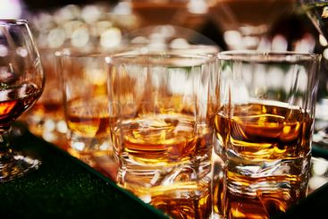 Glasses of whiskey on bar background. lots of glasses of...