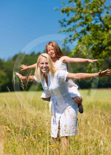 Mother with daughter in meadow