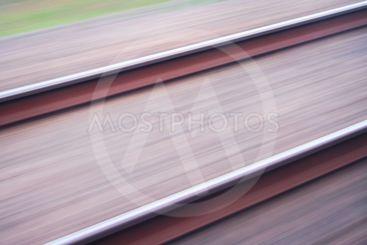 Järnvägsspår med oskarp bakgrund på grund av fart