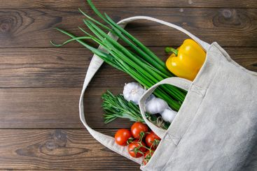 Woven bag of different health food on dark wooden table...