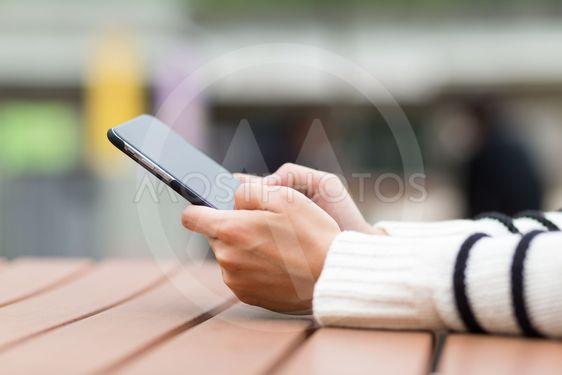 Woman use of mobile phone at outdoor cafe