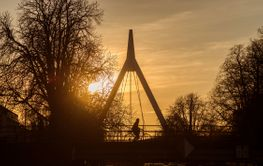 Silhouette of woman on bicycle on suspended bridge under...