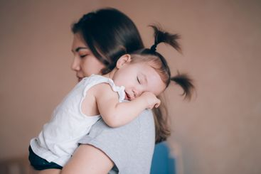 Young mother holding her little child girl.