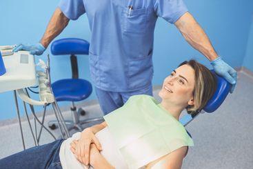 Dentist examining a patient's teeth using dental...