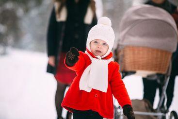 portrait of pretty little girl in red coat enjoying...