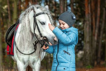 Little girl portrait, stands next to a white pony...