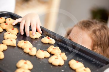 Close up of a little girl taking a cookie behind her...