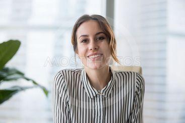 Smiling businesswoman looking at camera webcam make...