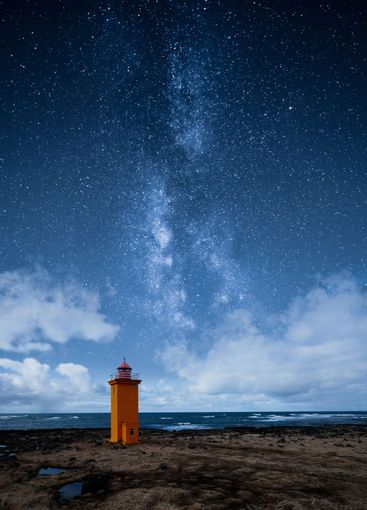 An orange lighthouse by the ocean at night with epic...