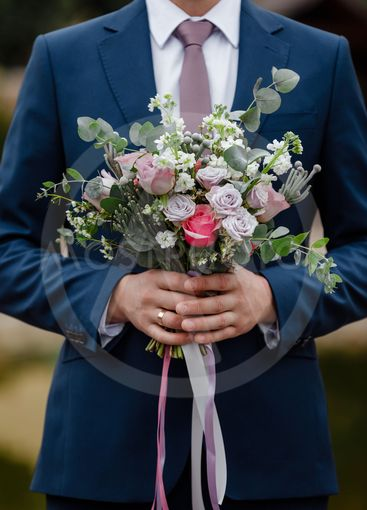 Stylish groom are holding bridal bouquet. Wedding...