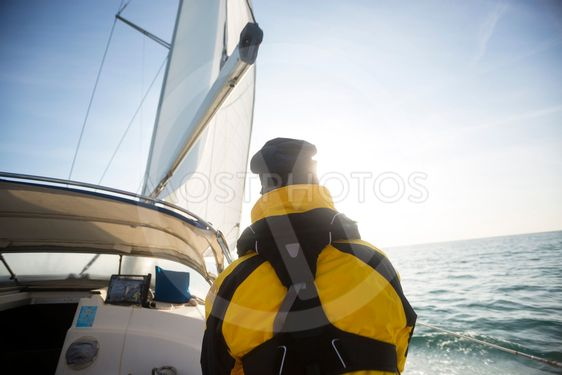 Rear View Of Mature Man Sailing On Yacht