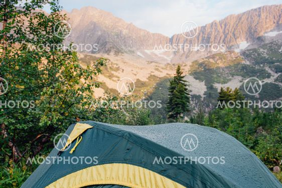 Green tent in forest at foot of mountain range. Hiking...