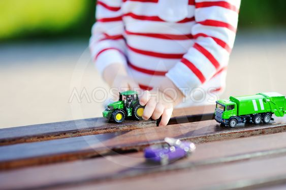 Toddler boy playing with toy cars close up