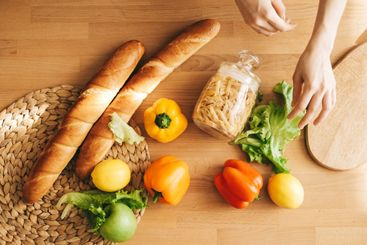 Baguette, pasta and fresh vegetables on a wooden table...