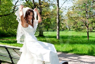 beautiful young bride sitting on a park bench