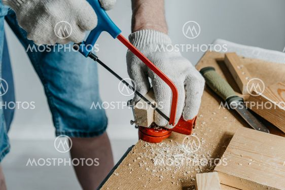 A man in work gloves is sawing a small block of wood...