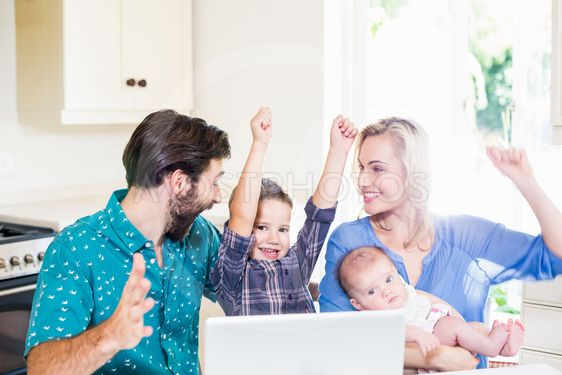 Excited parents and kids using laptop in kitchen
