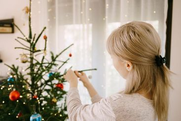 The blonde is decorating the Christmas tree at home.
