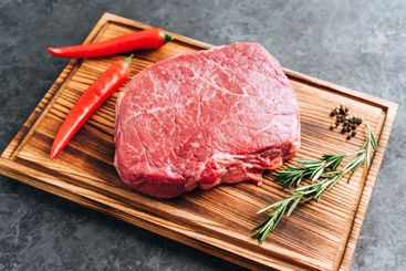 Raw beef steak on wooden board and black background with...
