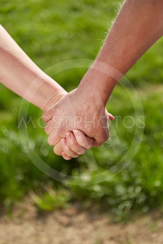 Old man and woman holding hands in nature