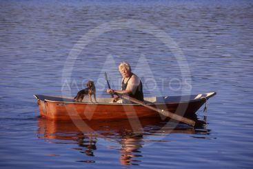 En man tar en kvälsrodd med sin hund.