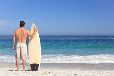 Man wirth his surfboard on the beach